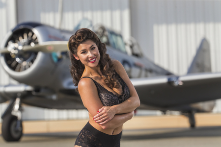 A brunette model in vintage clothing a WW II aircraft Stock Photo