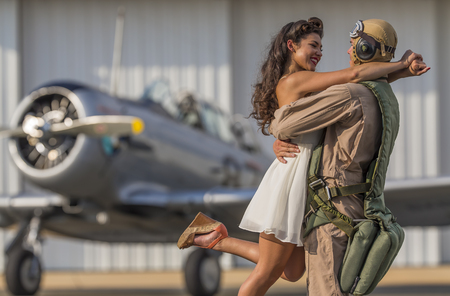 homecoming: A brunette model in vintage clothing with a pilot and a WW II aircraft