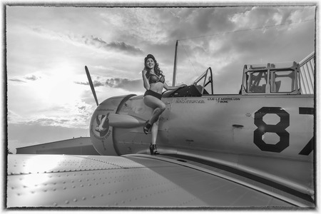 A brunette model in vintage clothing a WW II aircraft Editorial