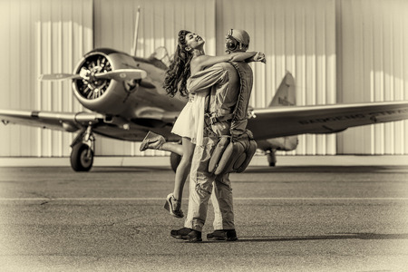 vintage dress: A brunette model in vintage clothing with a pilot and a WW II aircraft