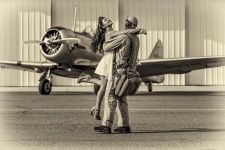 Un modelo morena en ropa de la vendimia con un piloto y un avión de la Segunda Guerra Mundial Foto de archivo