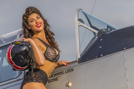 homecoming: A brunette model in vintage clothing a WW II aircraft Stock Photo