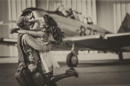 militaire sexy: Un modèle brune en vêtements vintage avec un pilote et un avion WW II