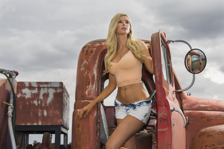 car model: A blonde model posing with an old truck in an outdoor environment