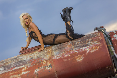 rusty car: A blonde model posing with an old truck in an outdoor environment