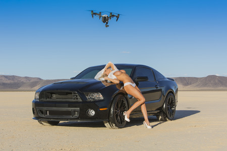 A nude model poses with a car in a desert environment Editorial