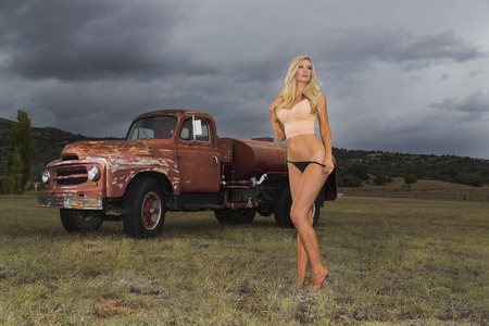 A blonde model posing with an old truck in an outdoor environment