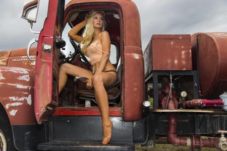 old truck: A blonde model posing with an old truck in an outdoor environment