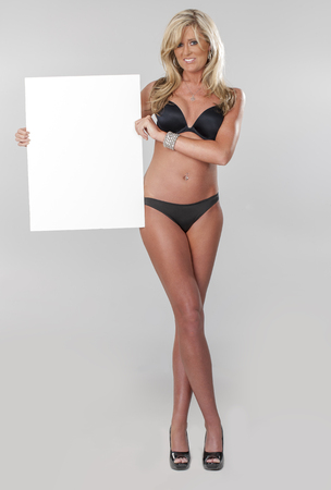 Beautiful young blonde in lingerie holding a blank board photo