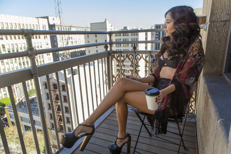 balcony: A brunette model on a balcony in a city environment