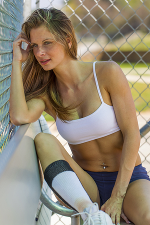 implied: Blonde female model posing outdoors at a baseball diamond wearing baseball equipment.