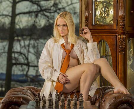 pechos: un modelo de mujer jugar al ajedrez, que presenta en posiciones eróticas Foto de archivo