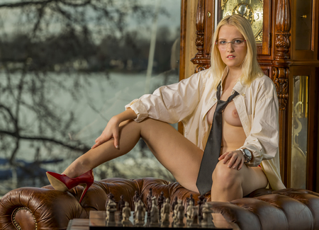 nude blonde woman: a female model playing chess, posing in erotic positions