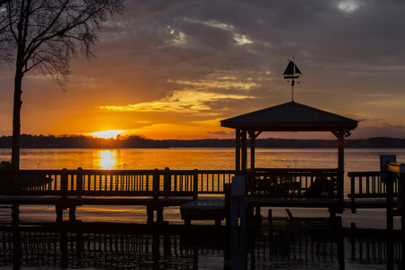 A colorful sunset over water with a pier in the foreground Archivio Fotografico