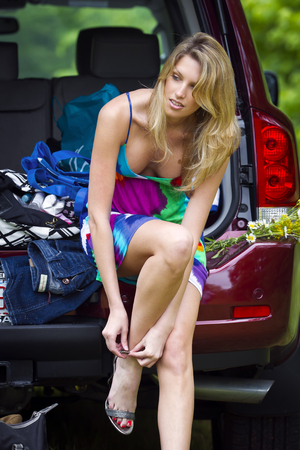 vistiendose: Un modelo Rubio poner en sus zapatos en la parte posterior de un SUV