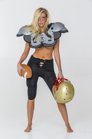 Blonde model posing in football equipment