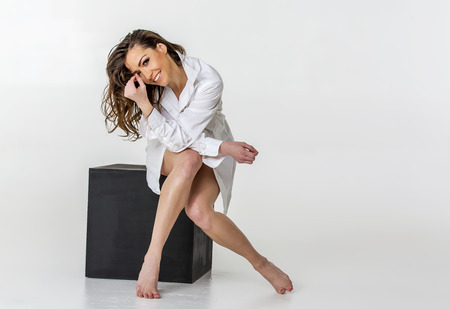 Implied brunette model posing in a studio environment