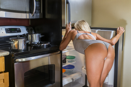 A blonde model searching for food in a home environment