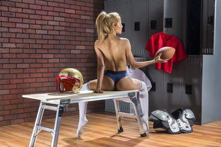 A model posing in a locker room environment with american football equipment. Imagens