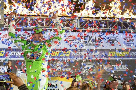 tx: Ft. Worth, TX - Apr 10, 2016: Kyle Busch (18) celebrates in victory lane after winning the Duck Commander 500 at the Texas Motor Speedway in Ft. Worth, TX.