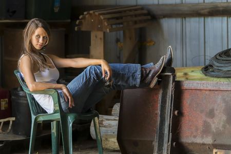 x country: model posing as a farmers daughter in a rural environment