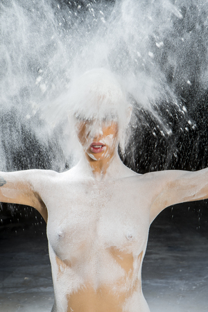 a nude female model with talcum powder posing in erotic positions