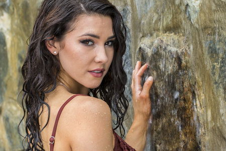 college dorm: Young brunette model posing against a waterfall