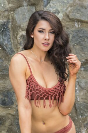 coed: Young brunette model posing against a waterfall