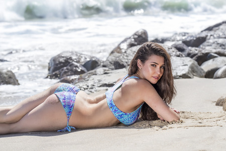 coed: A brunette model posing on a beach Stock Photo