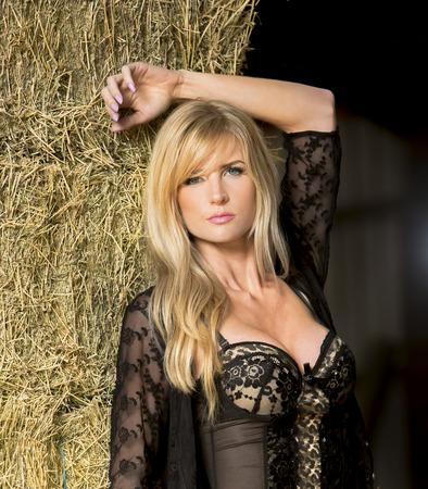 A blonde model posing in a barn