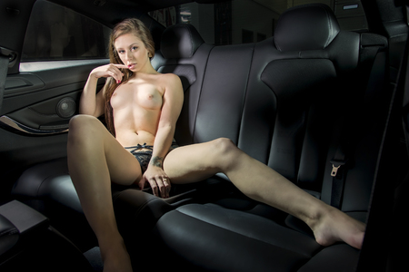 A brunette model posing with an automobile