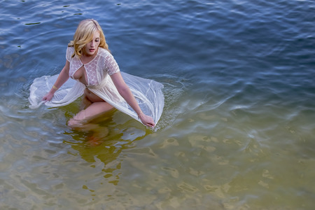 Blonde model posing in in water in an outdoor environment Stock Photo