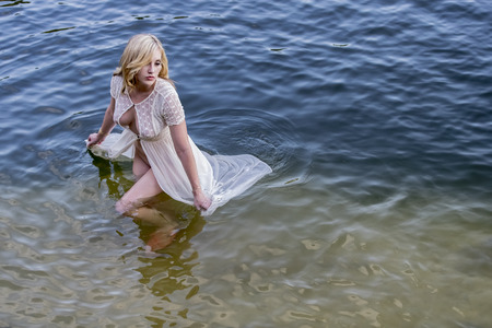 see through: Blonde model posing in in water in an outdoor environment Stock Photo