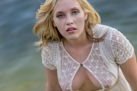 Blonde model posing in in water in an outdoor environment Imagens