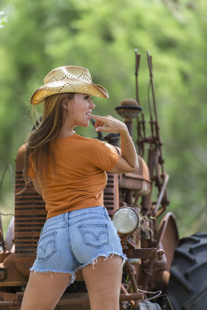 Brunette model with an old tractor Stock Photo
