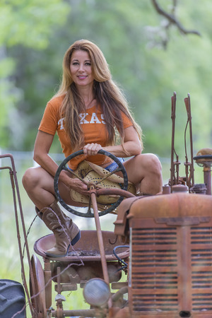 old tractor: Brunette model with an old tractor Stock Photo