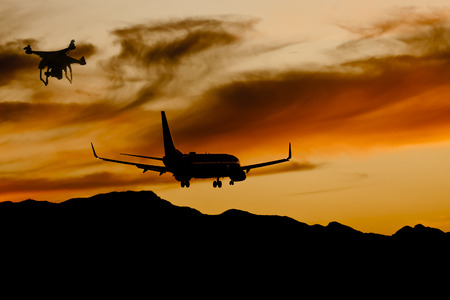 Commercial aircraft landing at an airport at sunset with a drone flying in controlled airspace