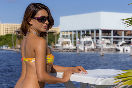 A brunette model poses in an outdoor environment