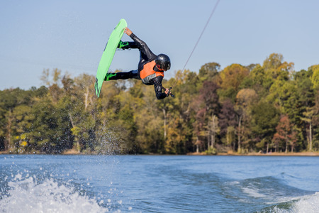 A young athlete wake boards on a body of water