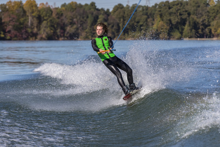 waterskiing: A young athlete wake boards on a body of water
