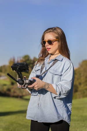 coed: A brunette coed flying a drone in the outdoors