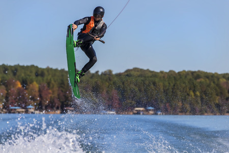 thrilling: A young athlete wake boards on a body of water