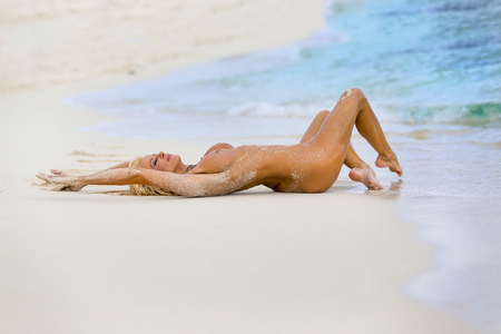 A nude blonde model enjoying a day at the beach