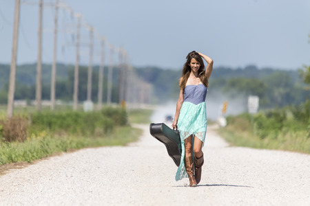 Female walking down a dirt road hitchhiking with a guitar case Stock Photo
