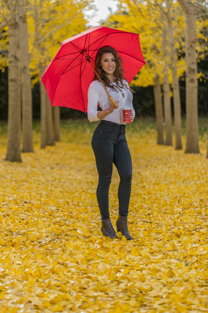 A beautiful brunette model with yellow fall foliage