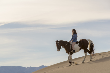 A female model riding her horse through the Mohave Desert Stock Photo