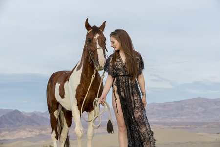 A female model riding her horse through the Mohave Desert Imagens