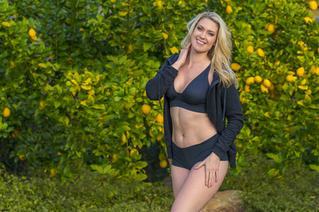 spandex: A blonde fitness model posing in an outdoor environment