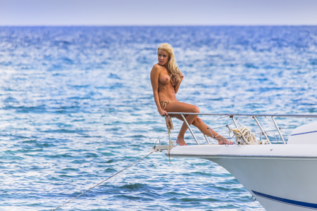 Blonde model posing on a boat in an outdoor environment