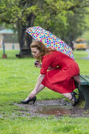 inclement weather: A redhead model posing in an outdoor environment in the rain